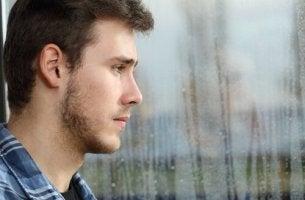 Adolescente triste mirando por la ventana