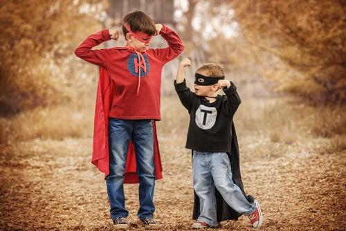 Hermano mayor y pequeño vestidos de superhéroes comparándose