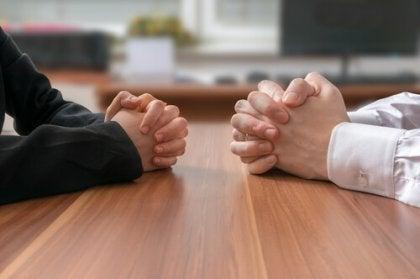 Manos de dos personas sobre una mesa mientras discuten