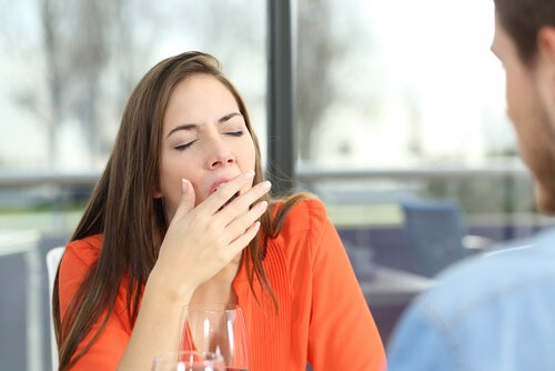 Mujer bostezando mientras habla con su compañero