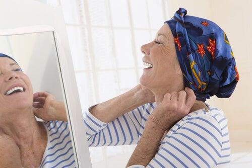 Mujer con cáncer mirándose al espejo sonriendo mientras se pone su pañuelo en la cabeza