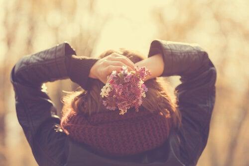 Mujer con los brazos levantados hacia atrás sujetando un ramo de flores