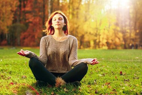 Mujer meditando con los ojos cerrados al aire libre