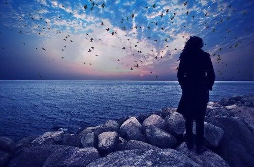 Mujer observando el mar al anochecer