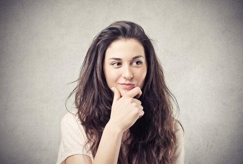 Mujer pensando con la mano en la barbilla