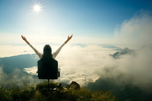 Mujer sentada con las manos arriba celebrando su éxito