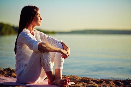 Mujer sentada tranquila mirando el mar