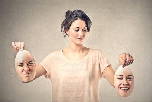 Mujer sosteniendo dos caras una enfadada y otra sonriendo