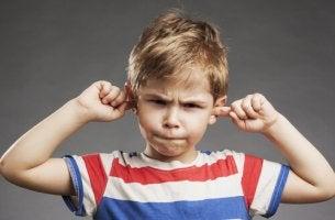 Niño tapándose los oídos no obedece