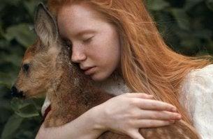 mujer abrazando un cervatillo