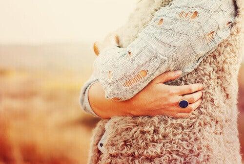 Mujer abrazándose antes de buscar aprobación