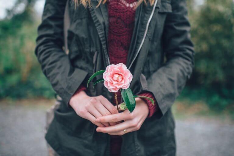 Mujer que sabe cuidarse con una flor en la mano