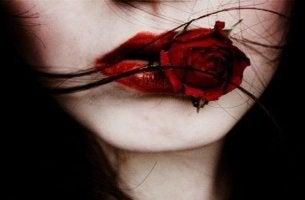 mujer con rosa roja en la boca