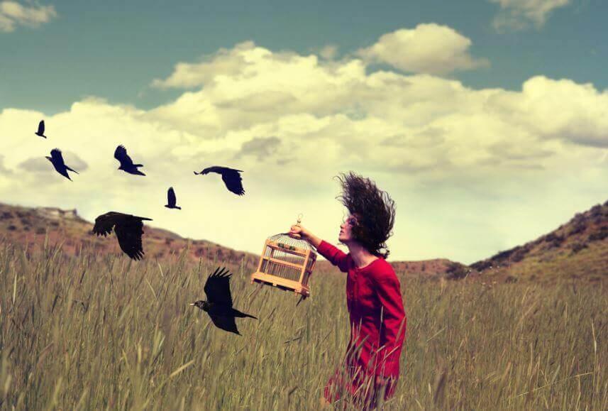 Mujer liberando pájaros de una jaula simbolizando como superar una traición