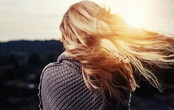 mujer rubia de espaldas triste por terminar la relación