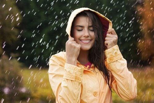 Mujers onriendo porque ve en la lluvia una oportunidad