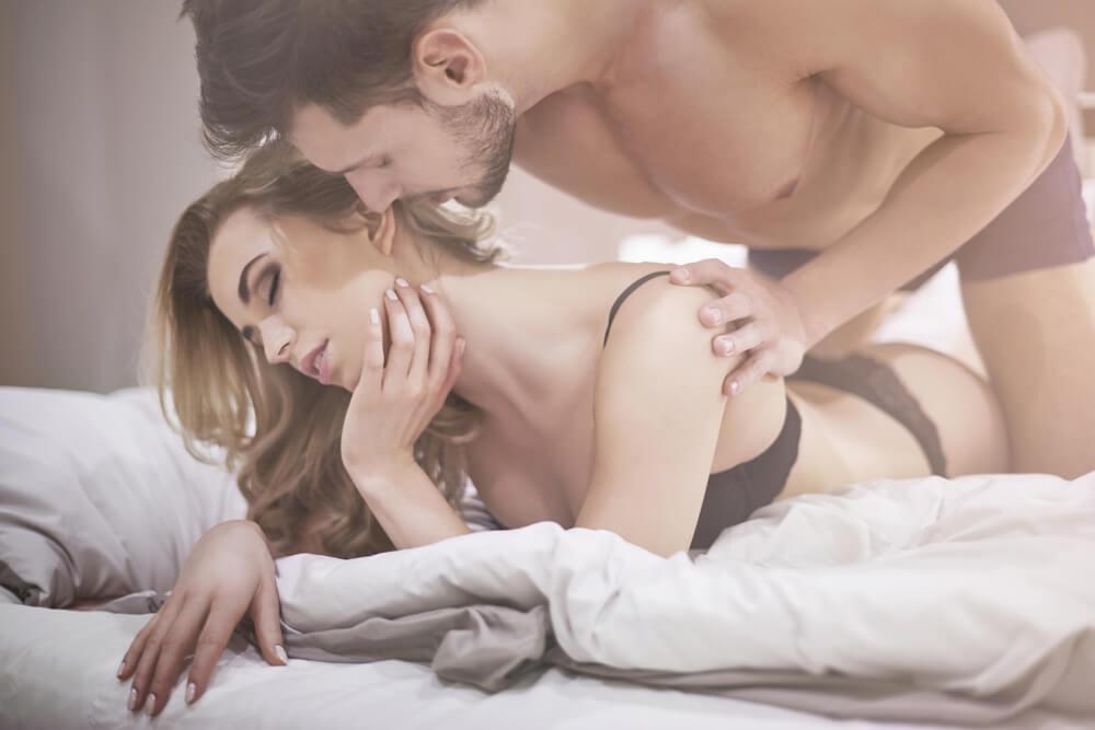 Mujer y hombre en la cama con erotismo