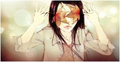 Niña con los ojos cubiertos por unas hojas