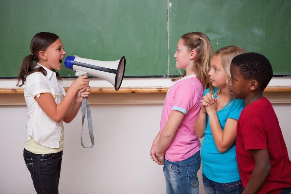 Niña gritándole a sus compañeros de clase