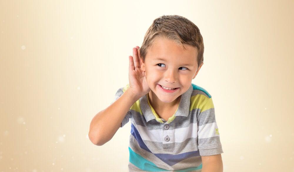 Niño con la mano en la oreja escuchando