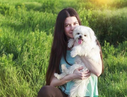Chica con un perro blanco entre sus brazos