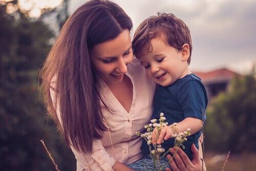 Madre cogiendo a su hijo en brazos mientras miran una flor