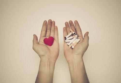 Mano con un corazón rojo y mano con cigarros