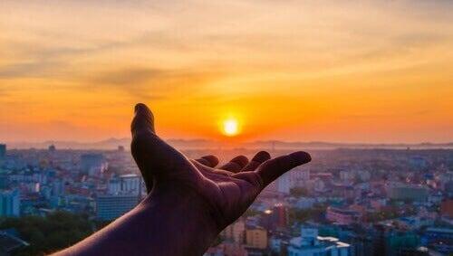 Mano señalando el sol al amanecer