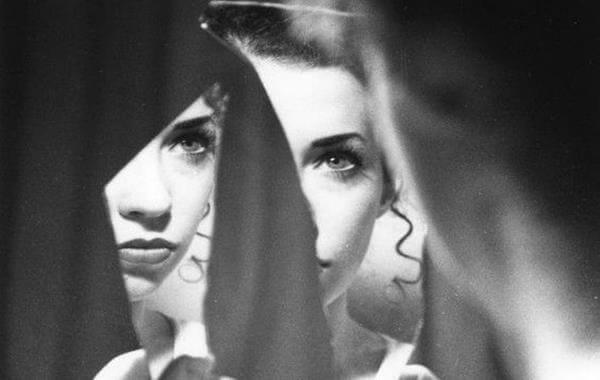Mujer mirándose en un espejo roto