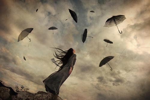 Mujer mirando a los paraguas volando en el cielo