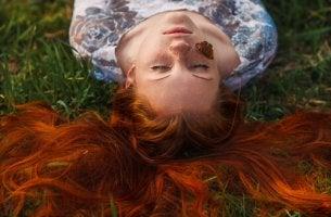 Mujer pelirroja tumbada con una mariposa en la cara