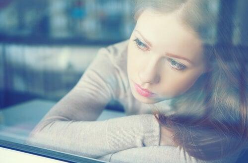 Mujer sintiendo culpa mirando por la ventana