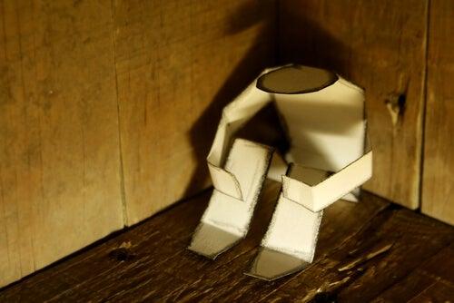 Muñeco de papel sentado en una esquina