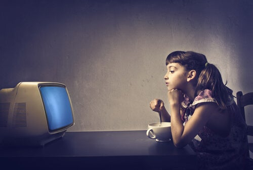 Niña comiendo cereales mientras ve la tele