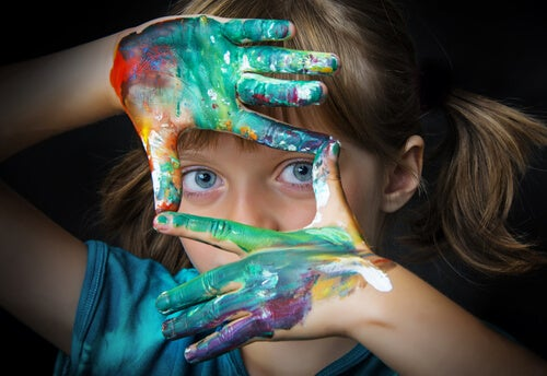 Niña con las manos llenas de pintura