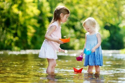 Niños compartiendo barcos de papel