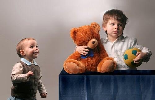 Niño agarrando un oso y un balón sin compartirlo con su hermano