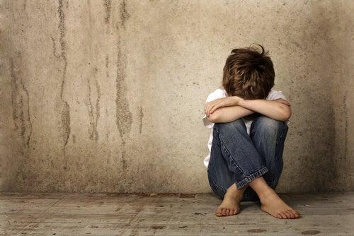 Niño triste sentado en el suelo con los brazos cruzados