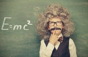 Niño vestido de Einstein resolviendo un problema