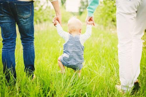 Padres agarrando a su hijo de las manos