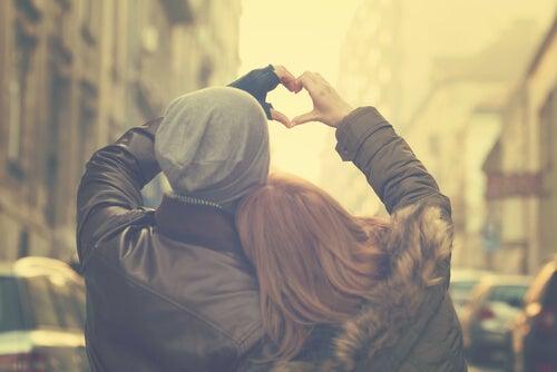 Pareja de espaldas formando un corazón con sus manos