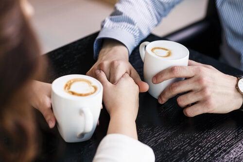 Pareja hablando agarrándose de las manos tomando café
