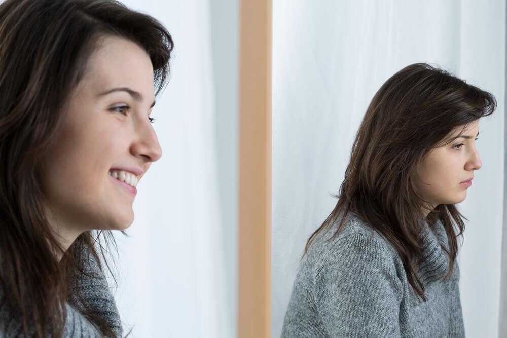 Mujer reflejada en el espejo triste
