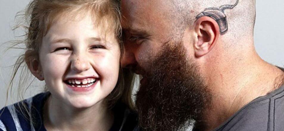 Papá e hija con implante coclear tatuado
