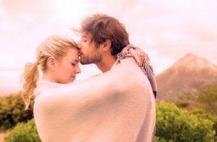 Hombre dándole un beso a su novia en la frente