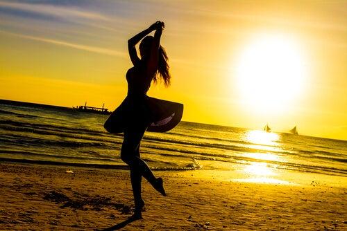 Mujer bailando en la playa