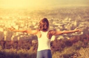 Mujer con los brazos abiertos subida en una montaña