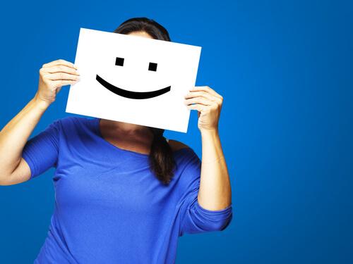 Mujer con un cartel de una cara sonriendo