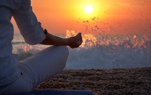 Mujer haciendo meditación en la arena de la playa