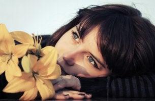 Mujer pensando con una flor sobre lo justo de la vida